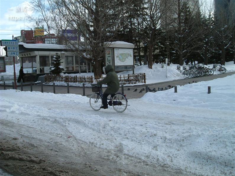 雪の上を自転車で走る札幌の人
